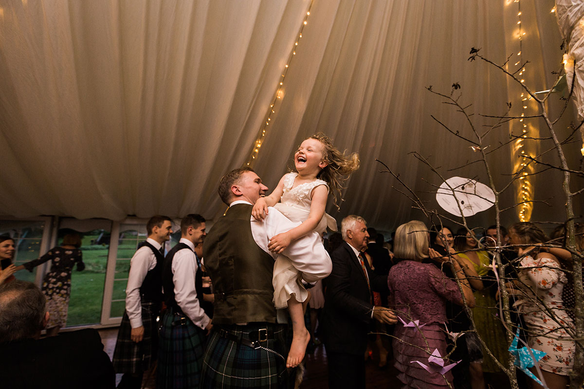 flower girl being carried by man in a kilt and laughing on dancefloor at marquee wedding in Perthshire