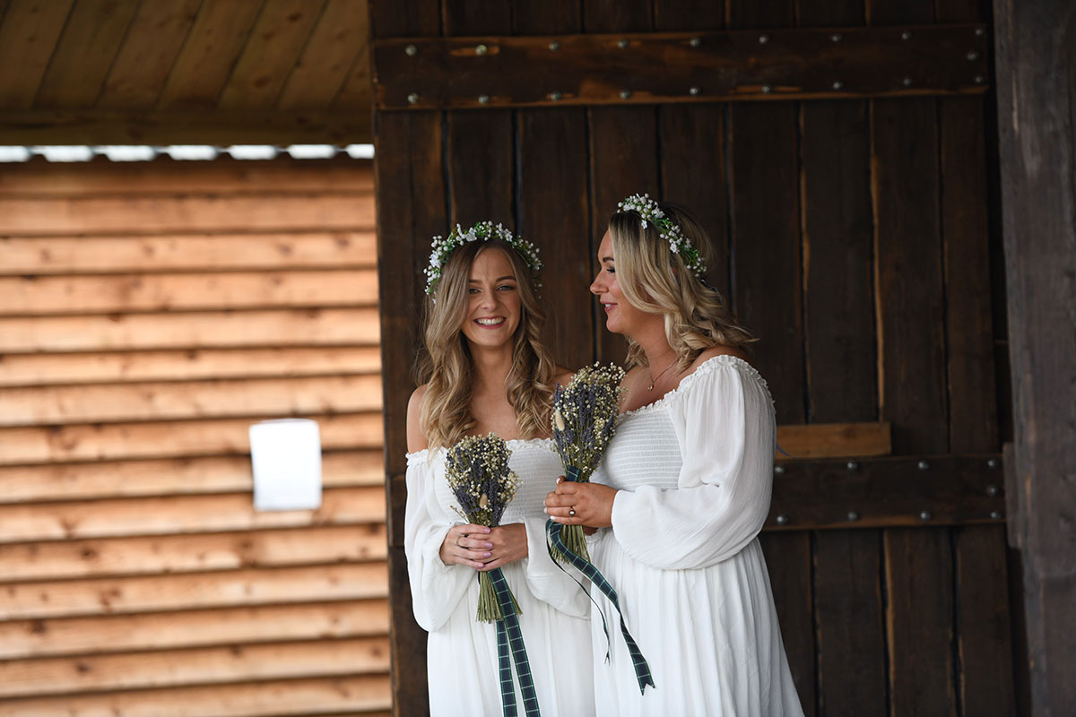 two bridesmaids wearing white off-shoulder dresses and floral crowns at The Gathering
