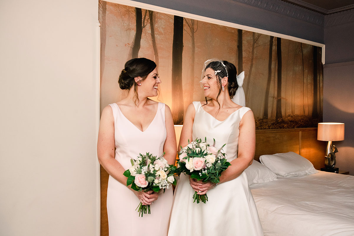 bride and bridesmaid smiling at each other in bedroom of Waterside Hotel in Inverness
