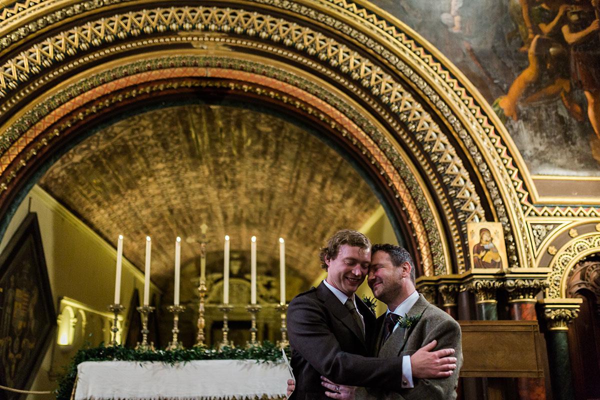 groom hugging best man in wedding chapel at Murthly Castle