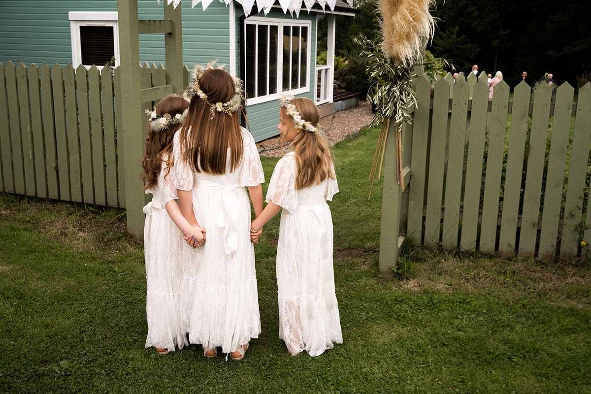 back of three flower girls wearing lace dresses from Etsy and daisy floral crowns