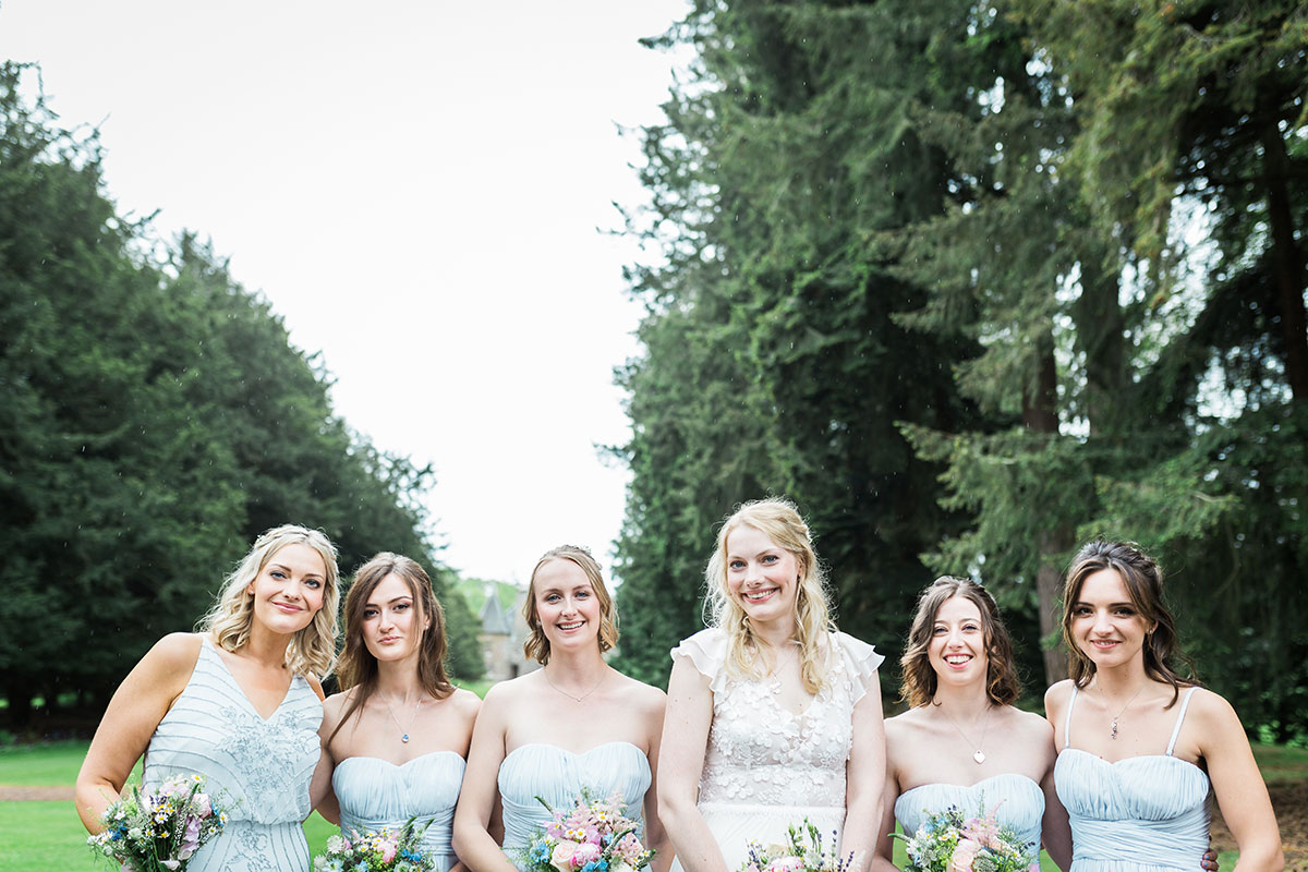 bride smiling with five bridesmaids wearing pale blue at Murthly Castle Perthshire