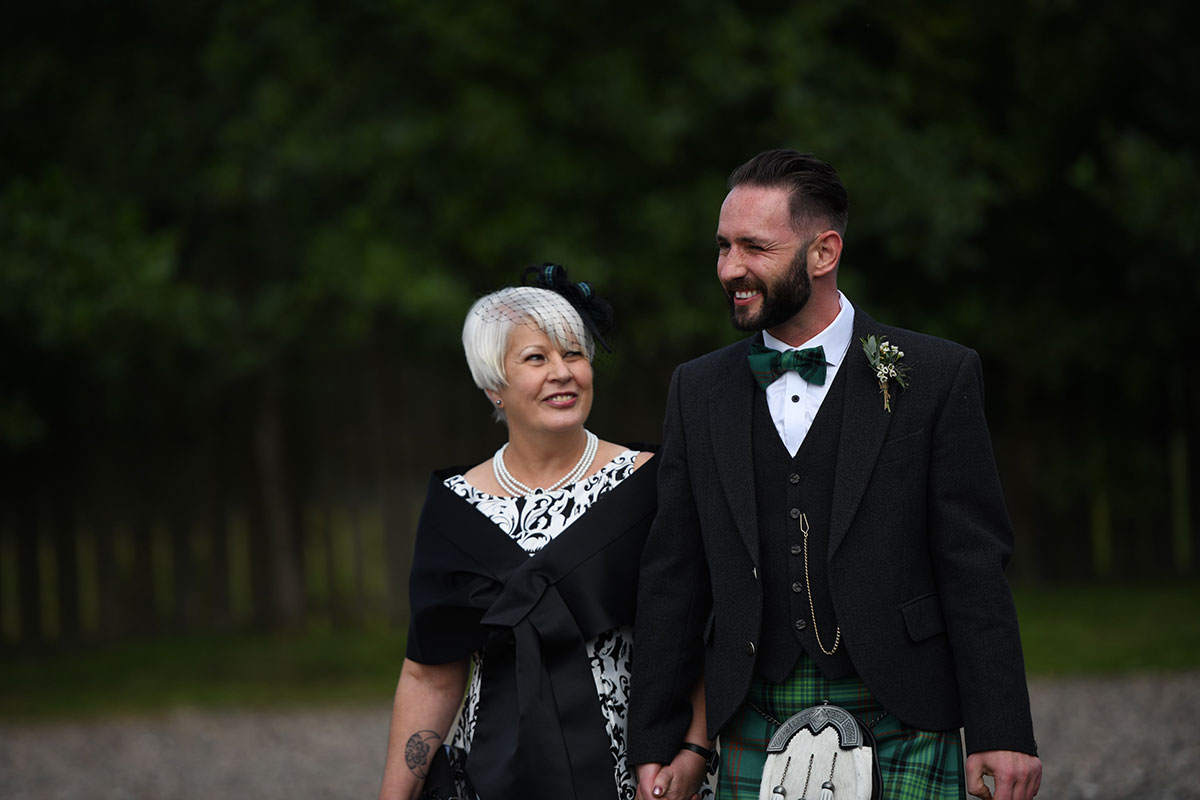 same sex wedding ceremony groom walking with his mum on wedding day