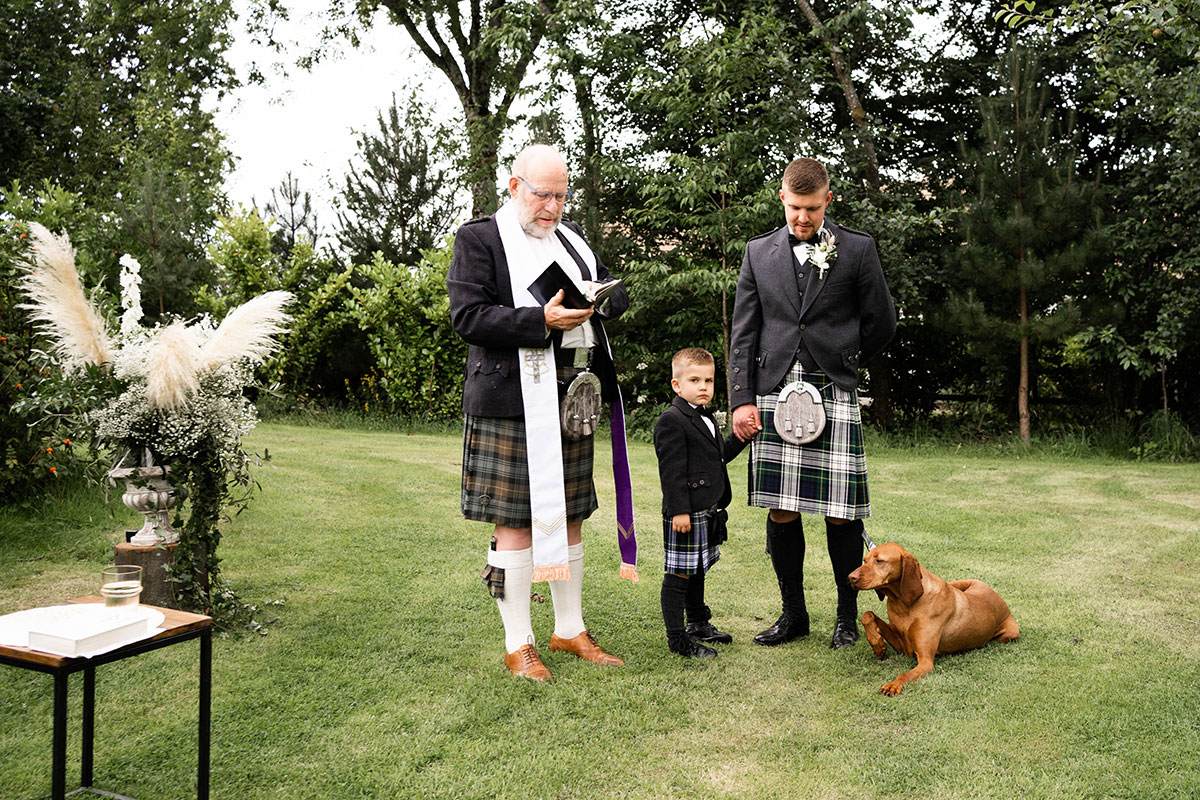 groom standing with son, dog and minister at outdoor Perthshire farm wedding