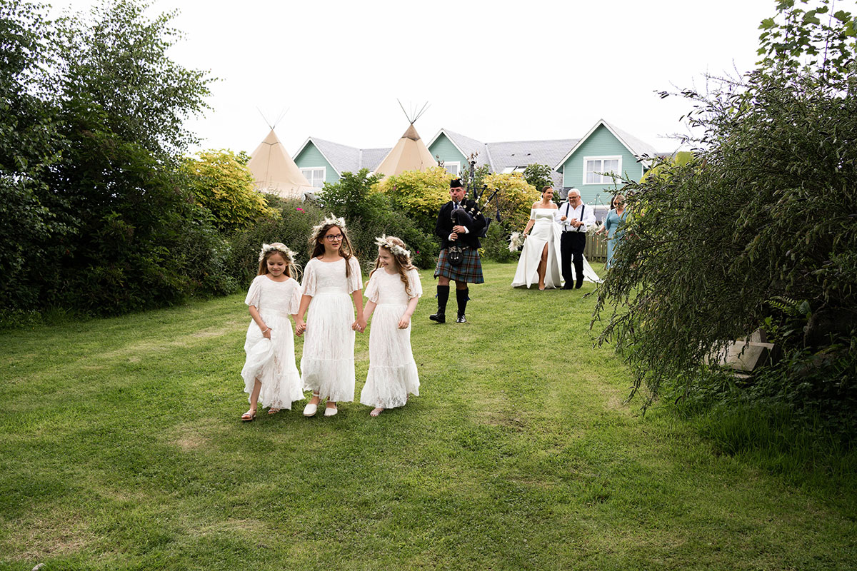 three flower girls leading wedding party and piper at outdoor Perthshire farm wedding
