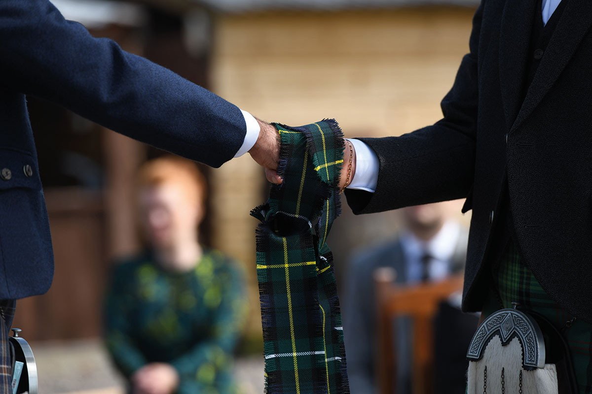 two grooms' hands performing hand fasting ceremony with tartan ribbon
