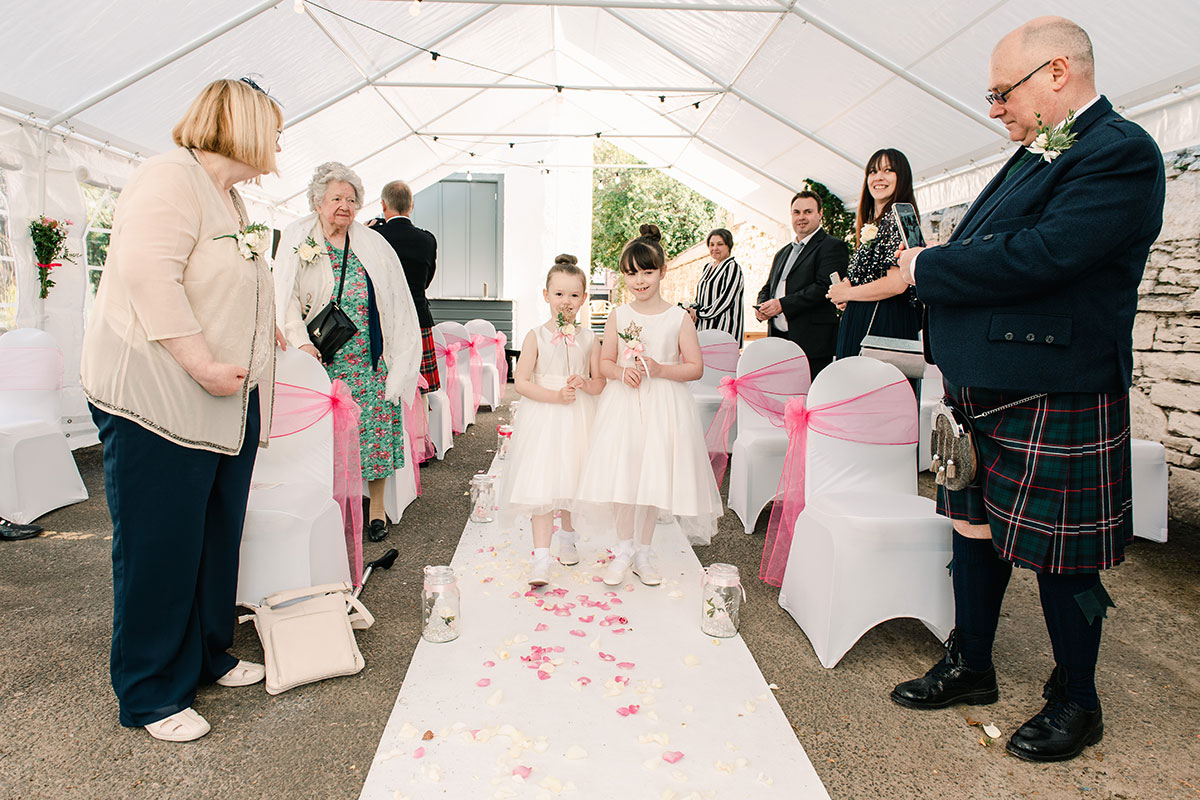 flower girls walking down aisle at marquee wedding ceremony at Waterside Hotel Inverness