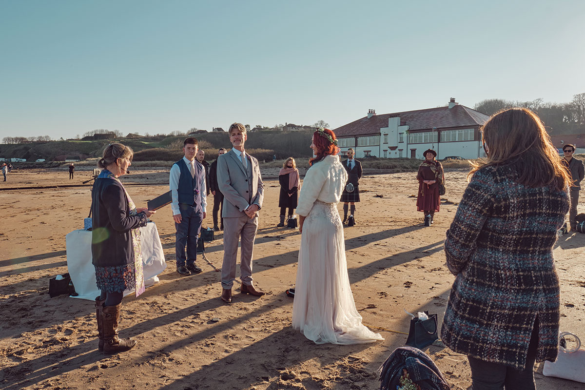Interfaith celebrant Jane Patmore performing wedding ceremony on a beach