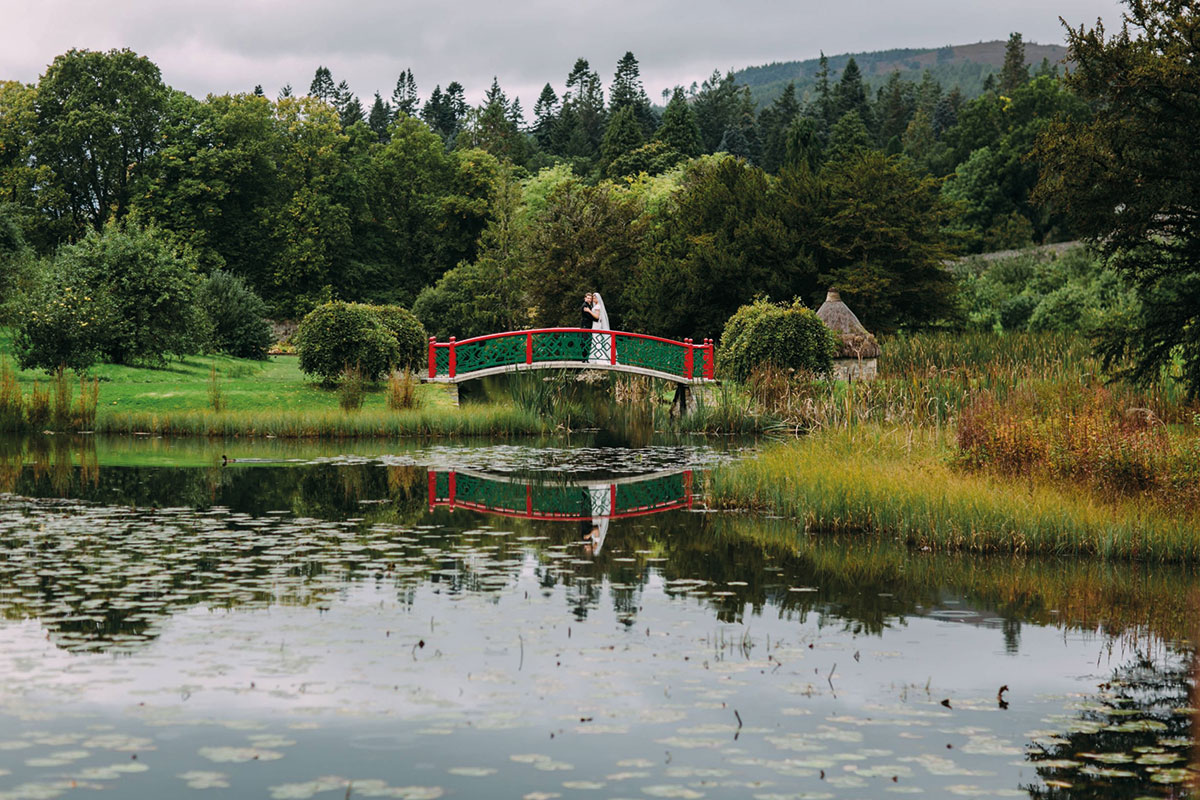 Bride and groom on a red and green bridge in the gardens of Blair Castle in Perthshire