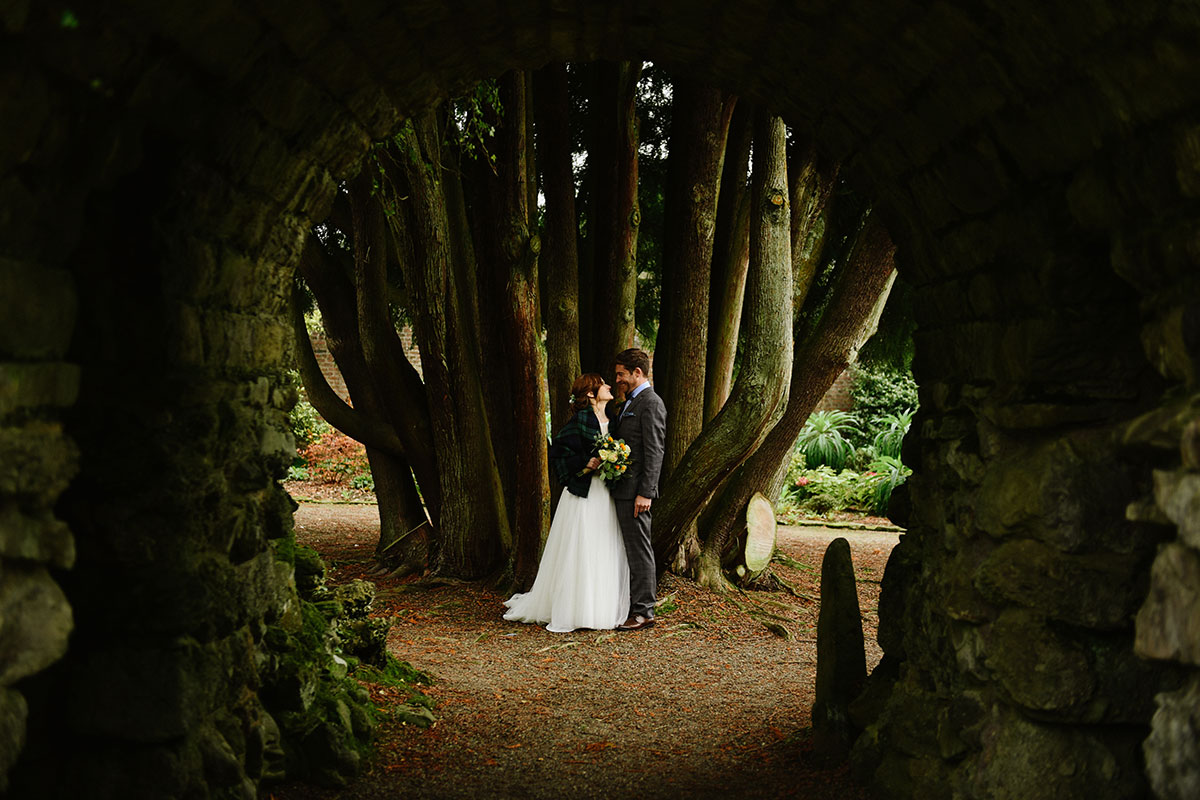 Bride and groom standing by the trunks of trees in the grounds of Culzean Castle in Ayrshire