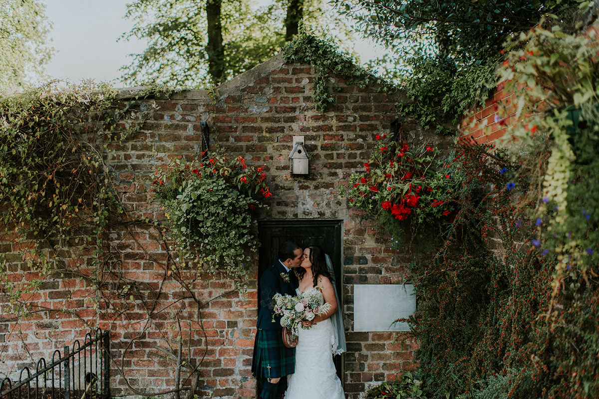 Bride and groom kissing in the walled garden at Bellahouston Park in Glasgow near House for an Art Lover