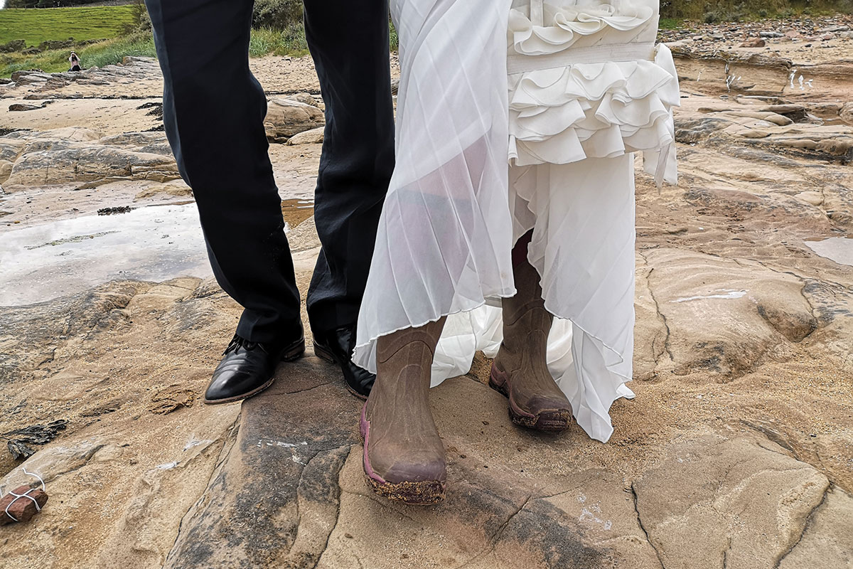 Legs of a lady wearing wellies and man wearing black trousers and smart shoes on a stone beach