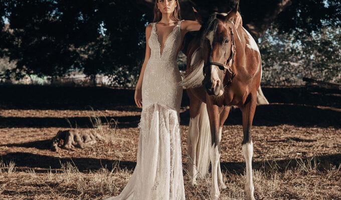 Model wearing style G-523 wedding dress by Galia Lahav standing next to a horse