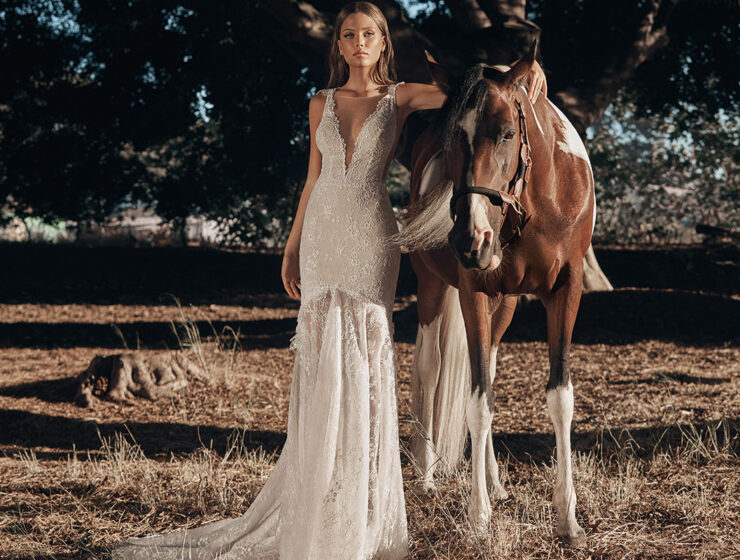 Model wearing style G-523 wedding dress by Galia Lahav standing next to a horse