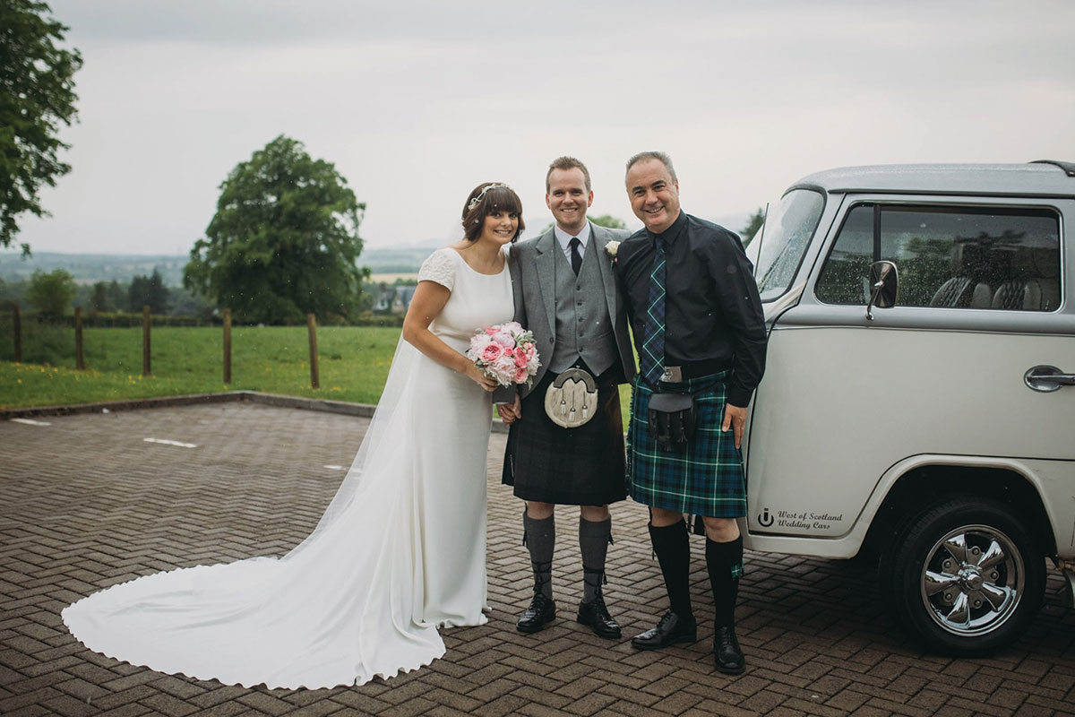 Celebrant Martin Turner with bride and groom standing next to wedding car