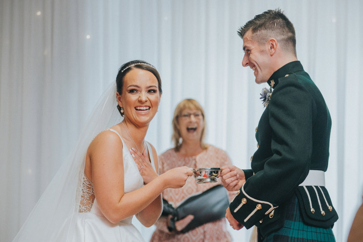 Celebrant Mo Ackroyd of Fuze Ceremonies with bride and groom doing quaich ritual during wedding ceremony