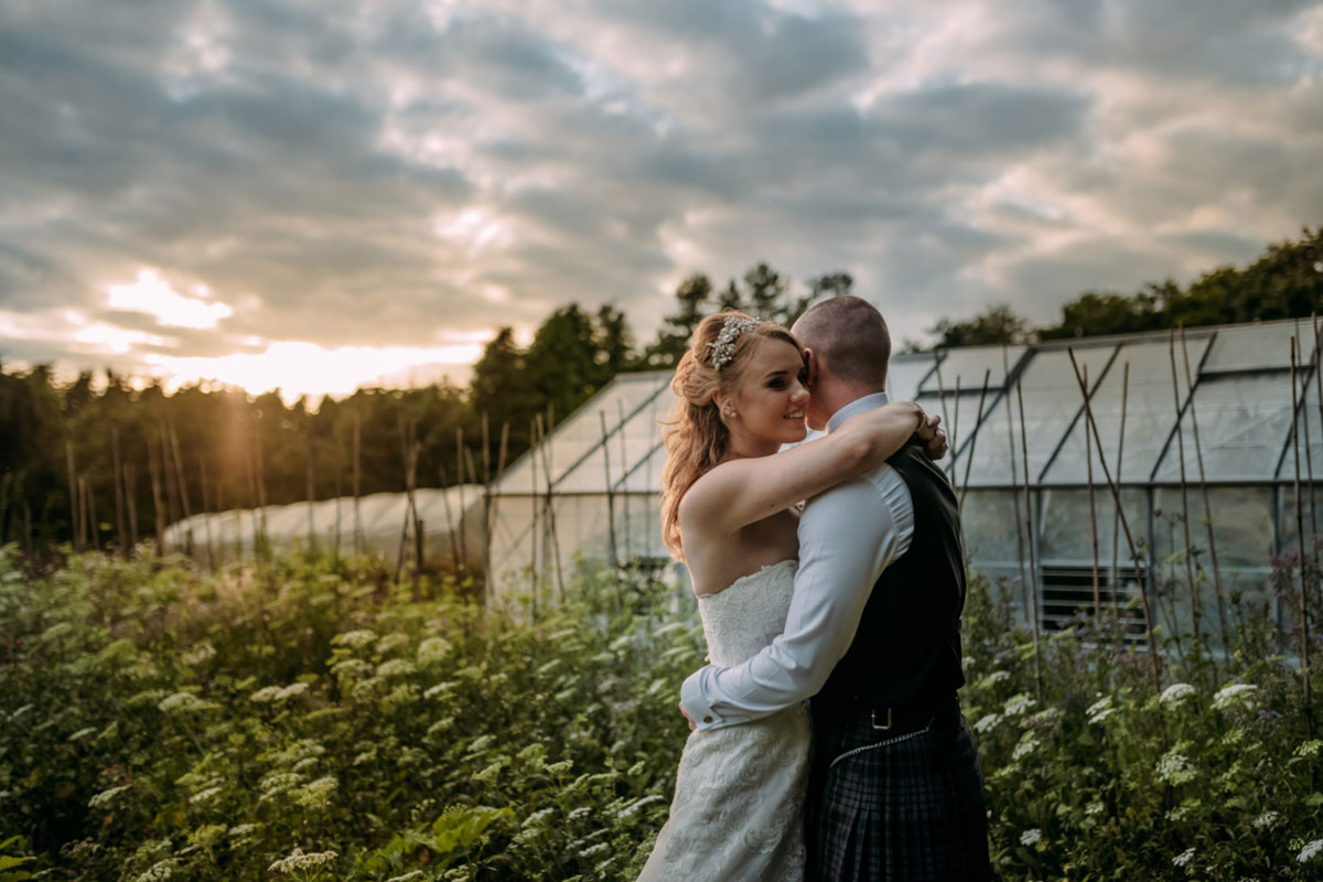 Bride and groom cuddling in the Kitchen Garden at Rufflets St Andrews