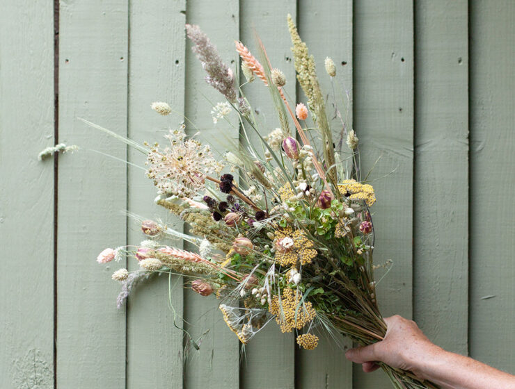 Dried flower bouquet against green wooden slatted background
