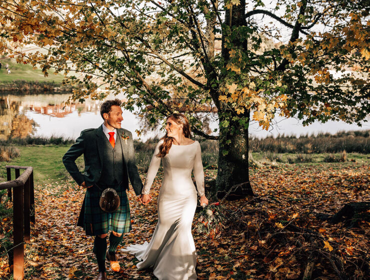 bride and groom holding hands and walking in autumn woodland with loch in background at Cardney Steading
