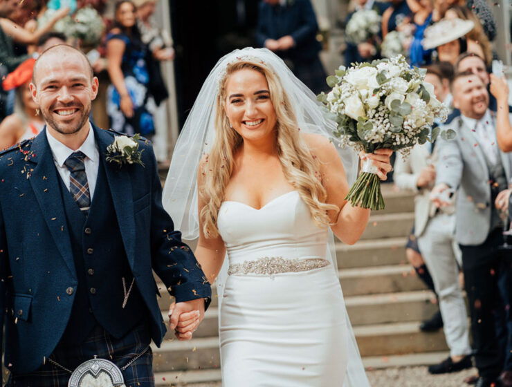 bride and groom holding hands outside Carlowrie Castle with guests in background