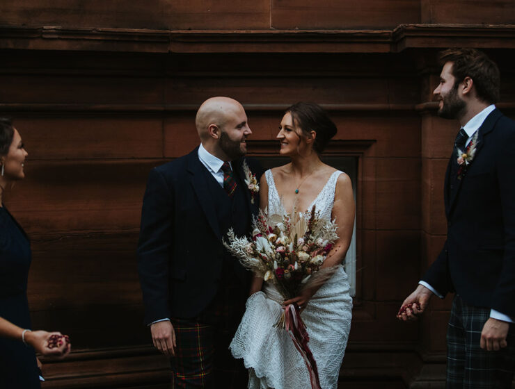 bride and groom outside The Waldorf Astoria Edinburgh with bridesmaid and best man looking on