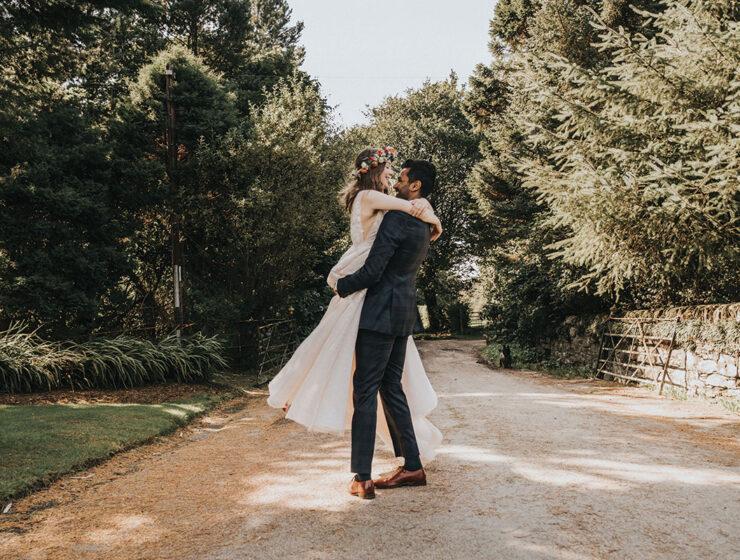 groom wearing suit spinning bride wearing floral crown around