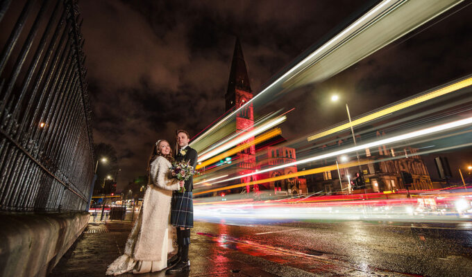 nighttime image of bride and groom outside Oran Mor with car lights long exposure effect