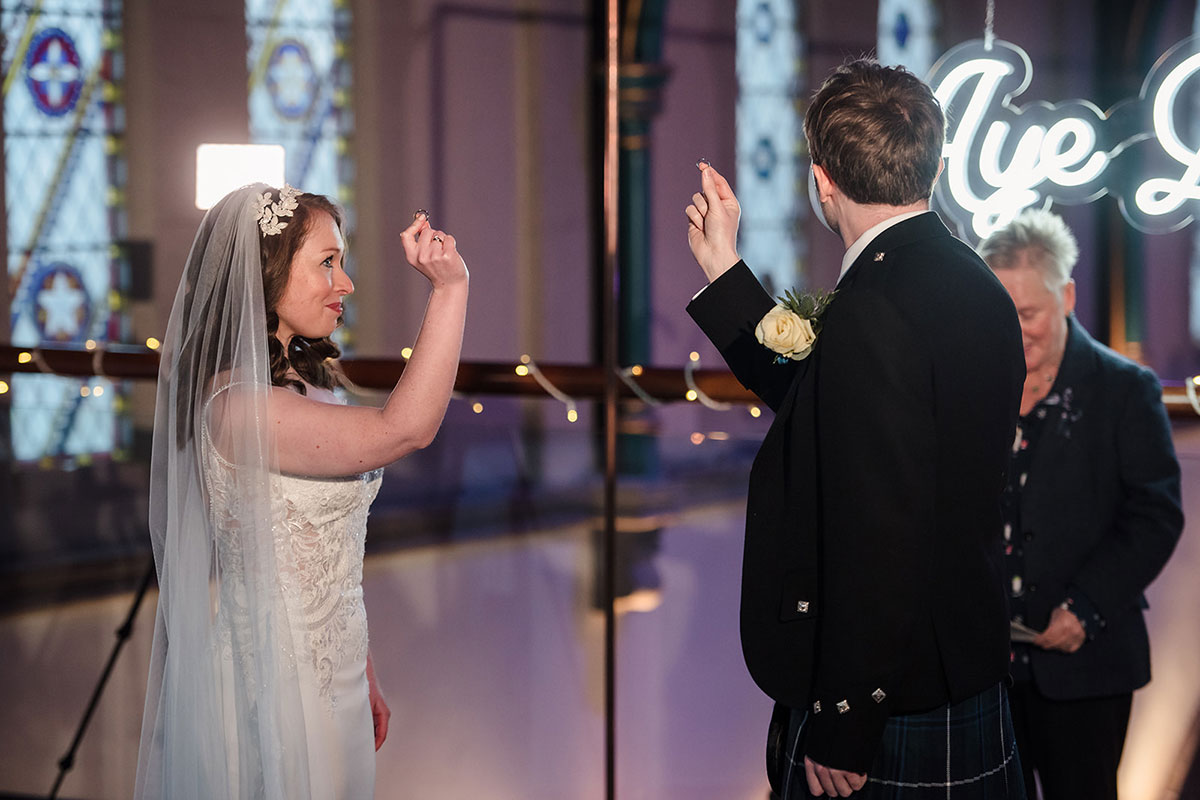bride and groom holding wedding rings in air during wedding ceremony at Oran Mor