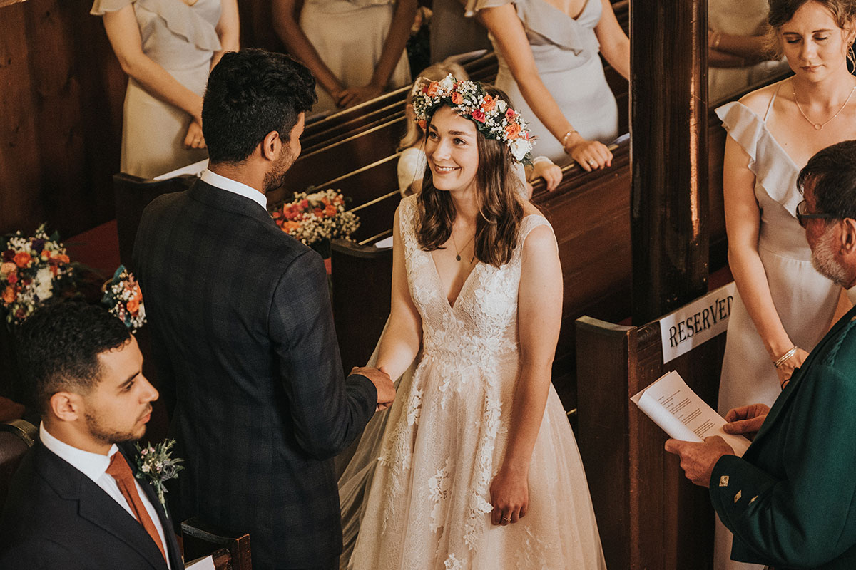 bride smiling into eyes of groom during wedding ceremony at Clachan Kirk in Kintyre