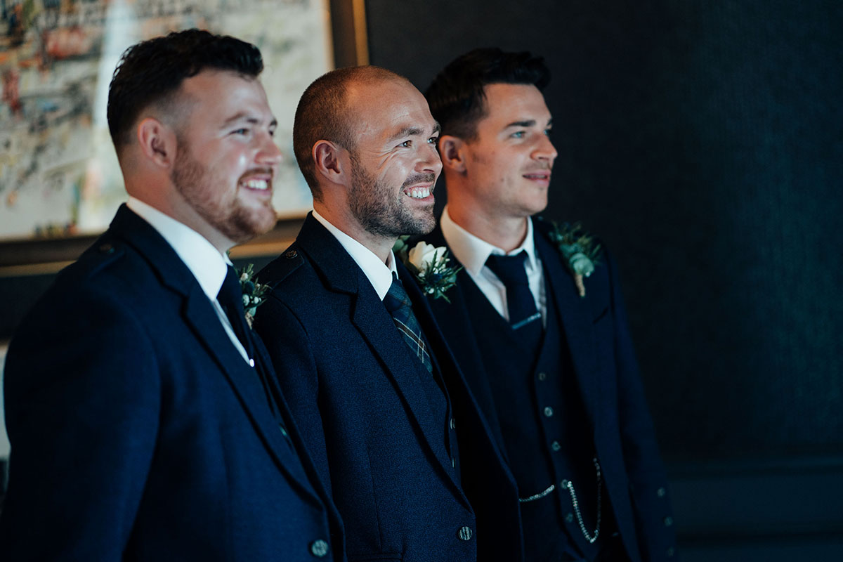 groom flanked by two best men smiling