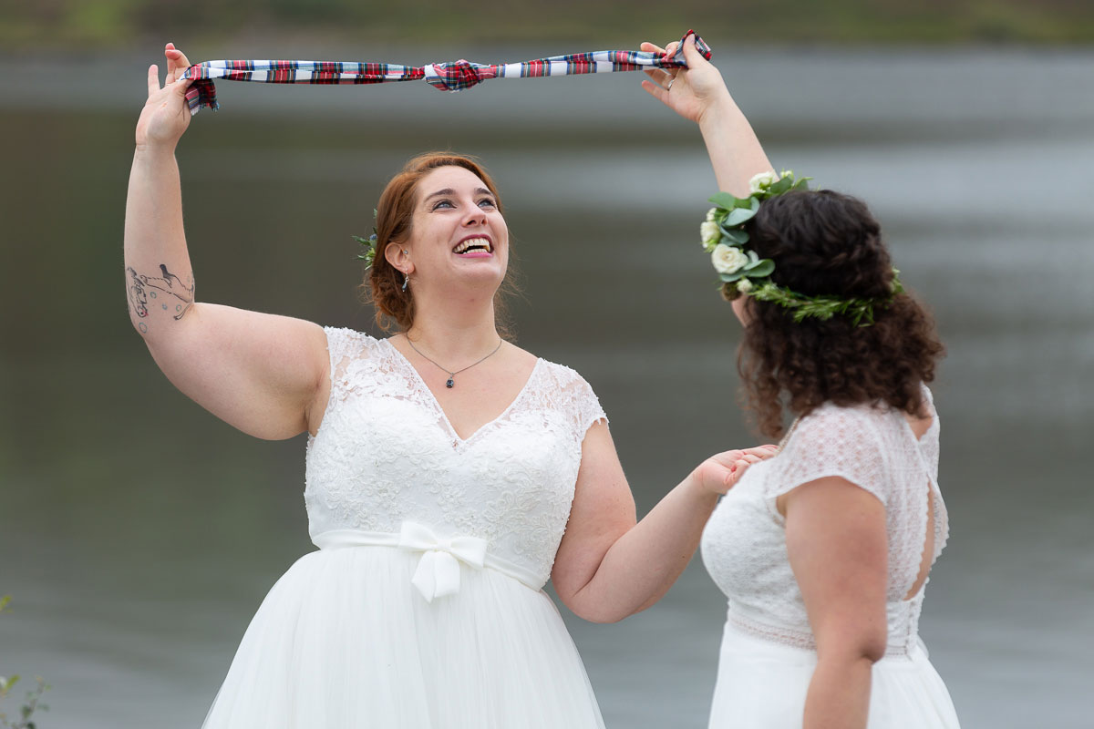 laughing brides holding tartan hand fasting ribbon in air during outdoor lesbian wedding ceremony on shore of Loch Turret Reservoir in Perthshire
