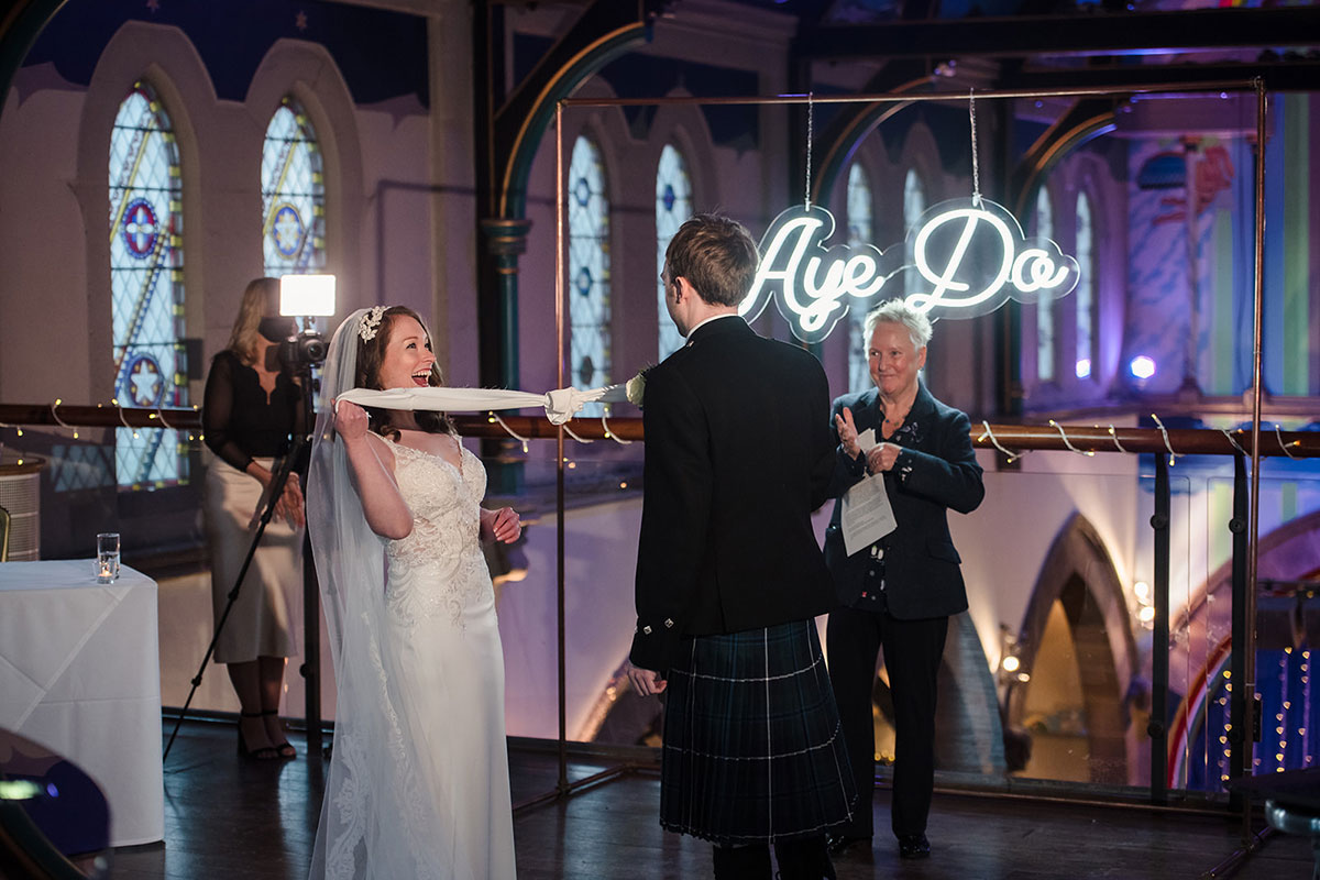 bride and groom laughing during hand fasting at wedding ceremony at Oran Mor