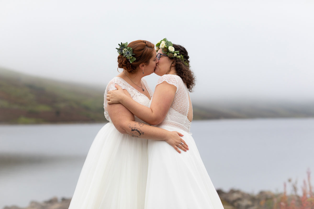 two brides kissing during lesbian wedding ceremony on shore of Loch Turret Reservoir in Perthshire