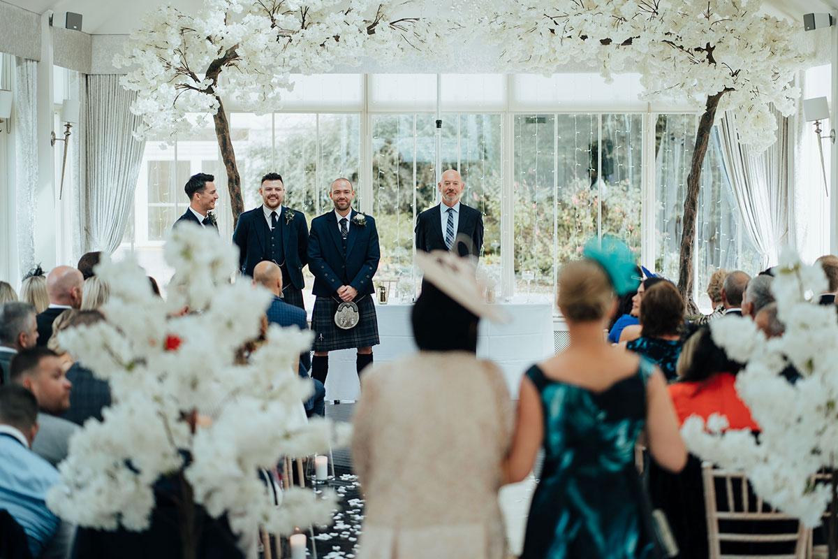 groomsmen look on as guests arrive in wedding marquee at Carlowrie Castle