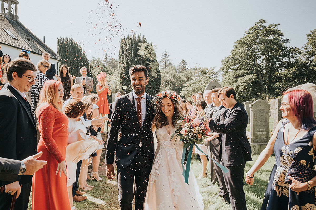 bride and groom being showered in confetti in the sunshine at Balinakill Country House in Kintyre