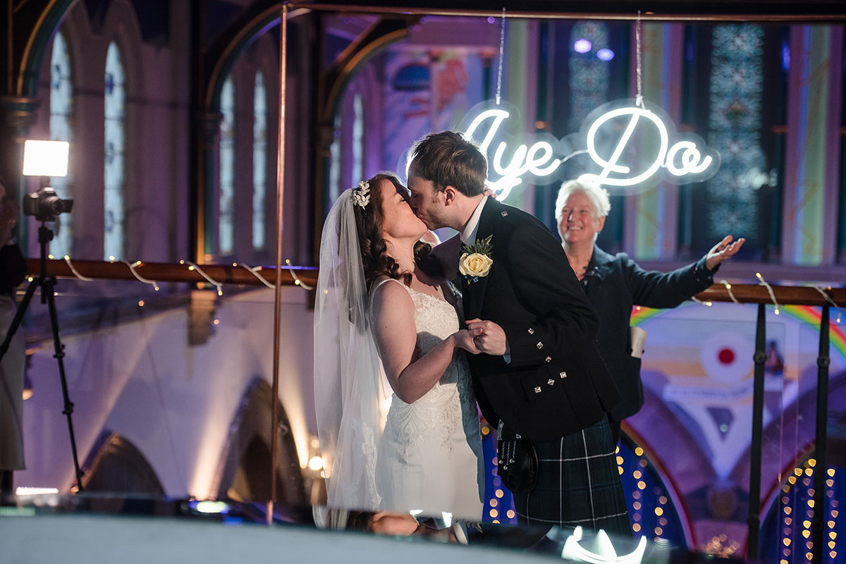 bride and groom kissing on mezzanine of Oran Mor with celebrant in background