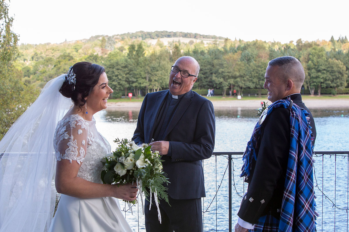 bride and groom laughing with minister during wedding ceremony at The Shore Loch Lomond