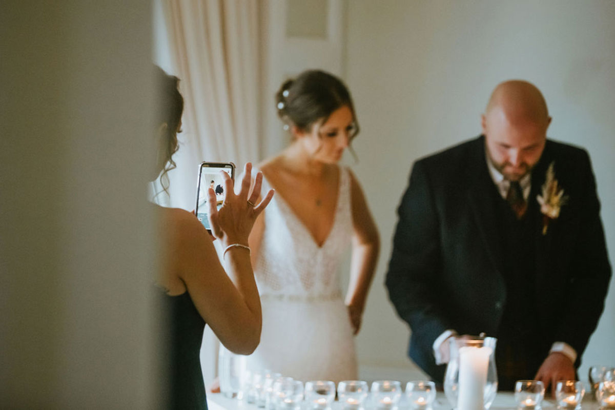 bride and groom lighting candles during wedding ceremony while bridesmaid takes a picture on mobile phone