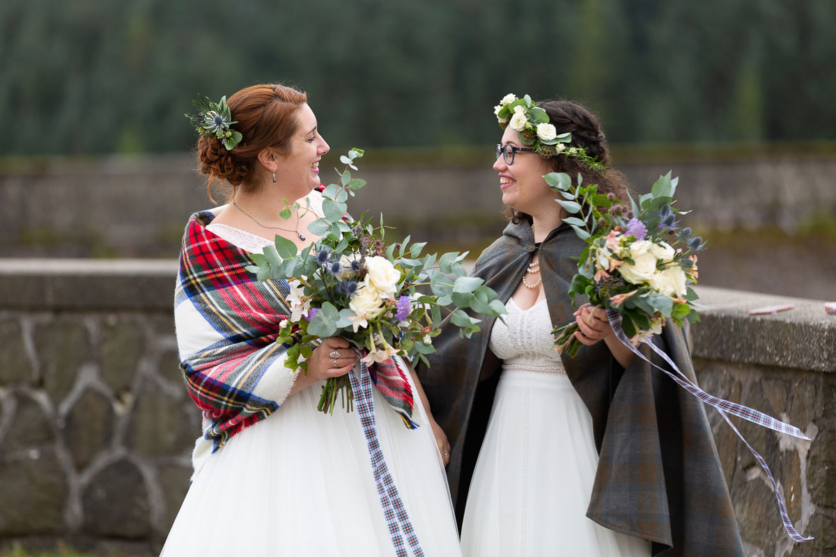 two brides smiling wearing shawl and cape and carrying bouquets by Eucalyptus Flowers during outdoor lesbian wedding ceremony on shore of Loch Turret Reservoir in Perthshire