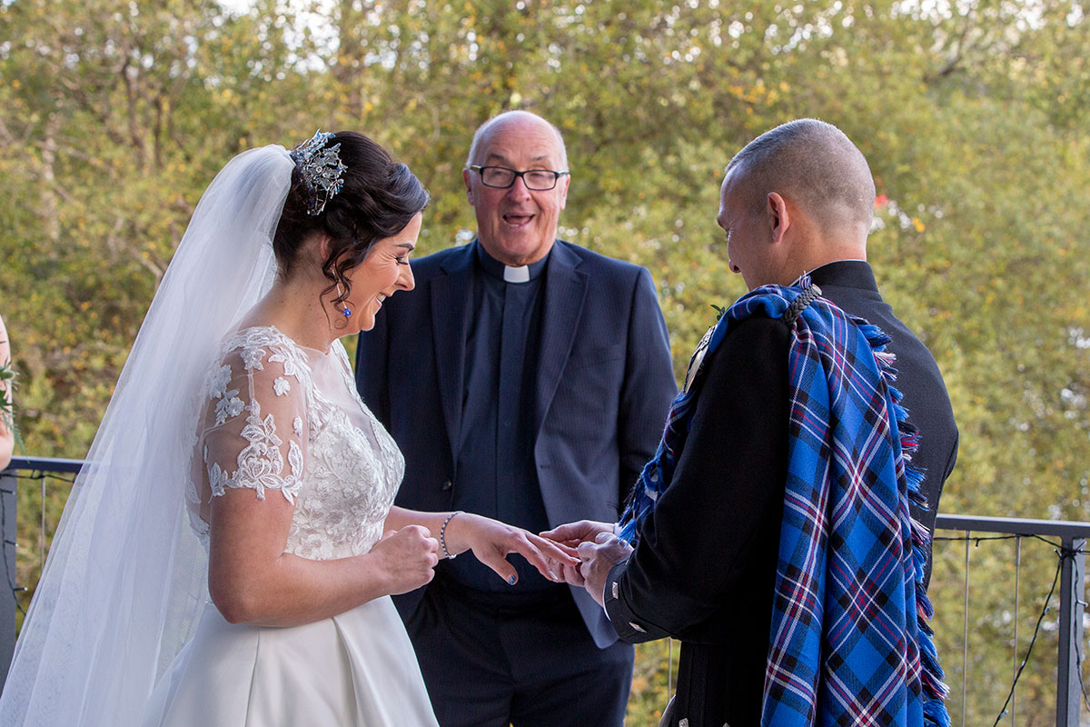 bride and groom exchanging wedding rings with minister
