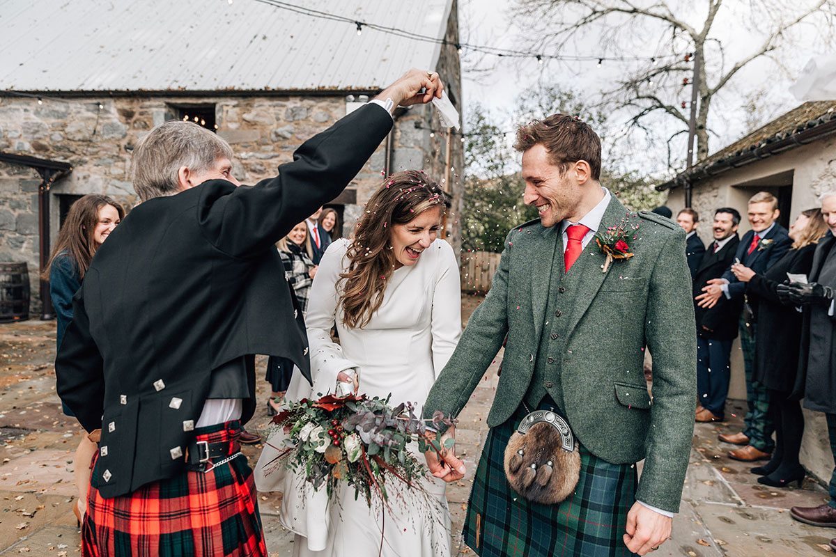bride and groom outside Cardney Steading with confetti being poured onto them by male guest