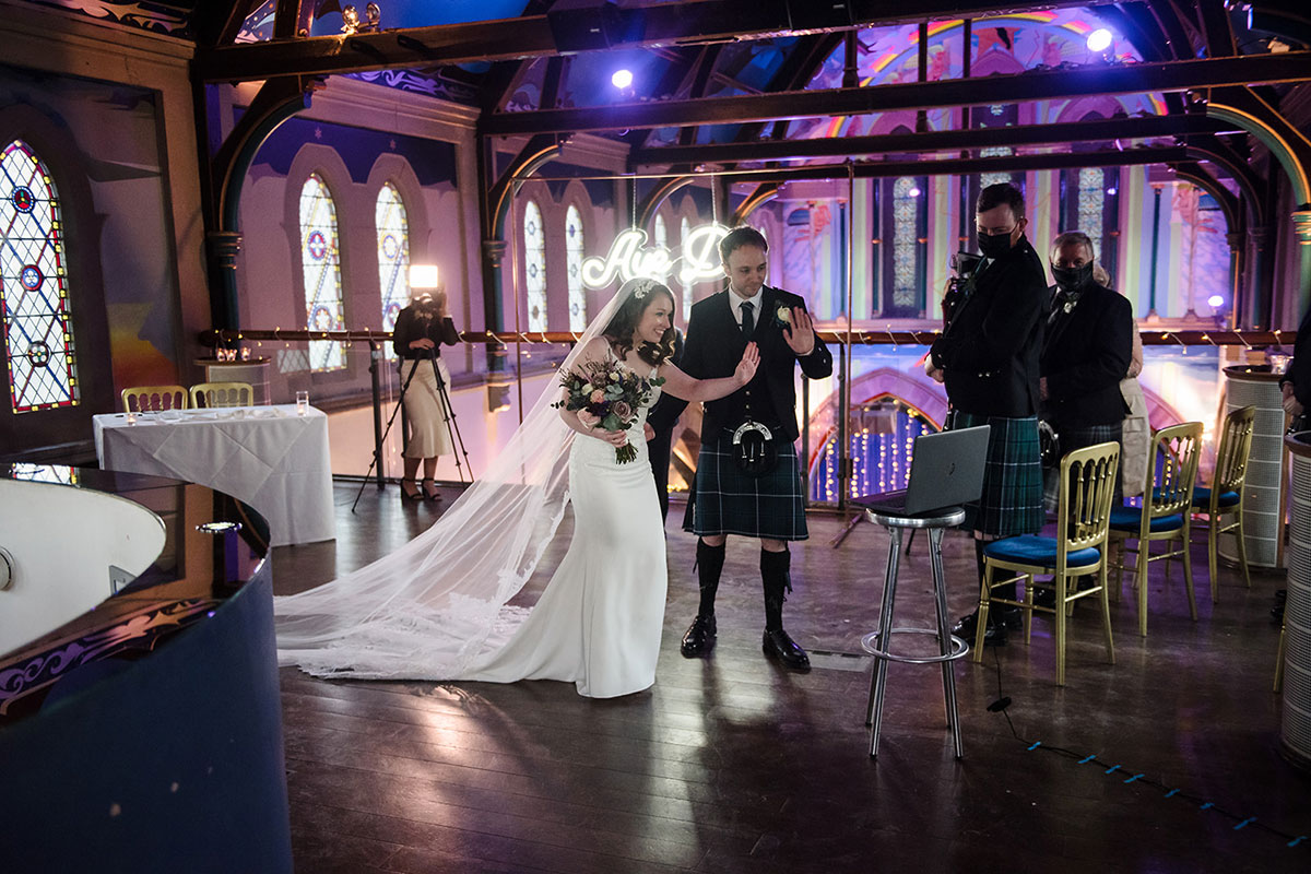 bride and groom waving to guests on laptop at live streamed wedding ceremony at Oran Mor