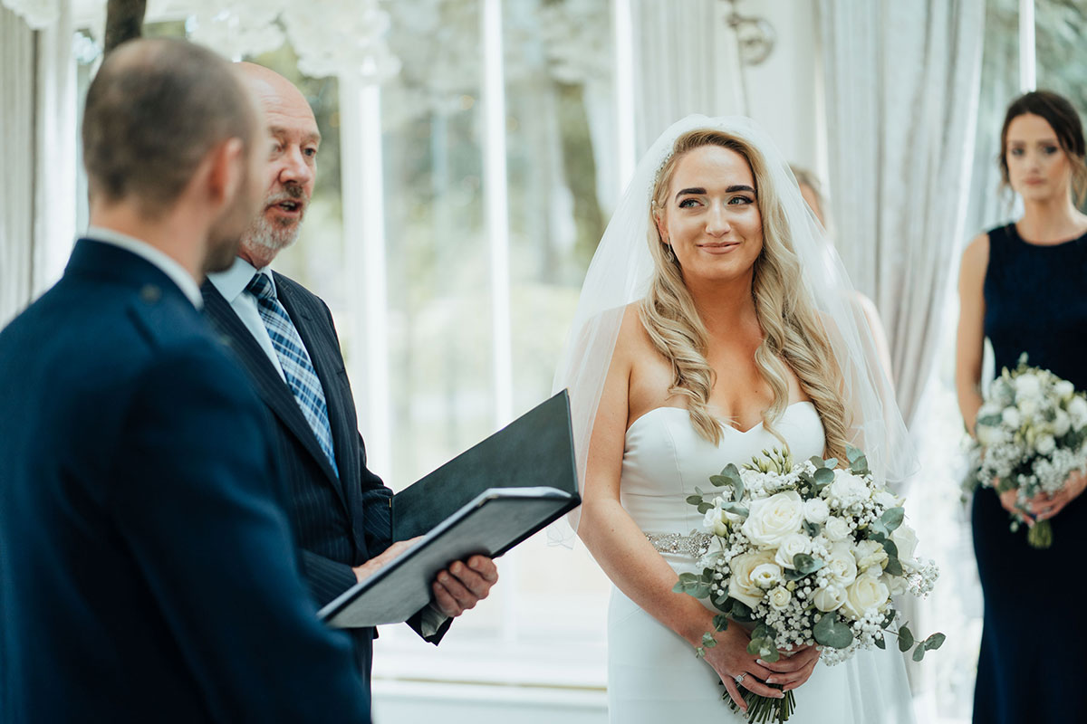 bride, groom and celebrant at wedding ceremony in Carlowrie Castle