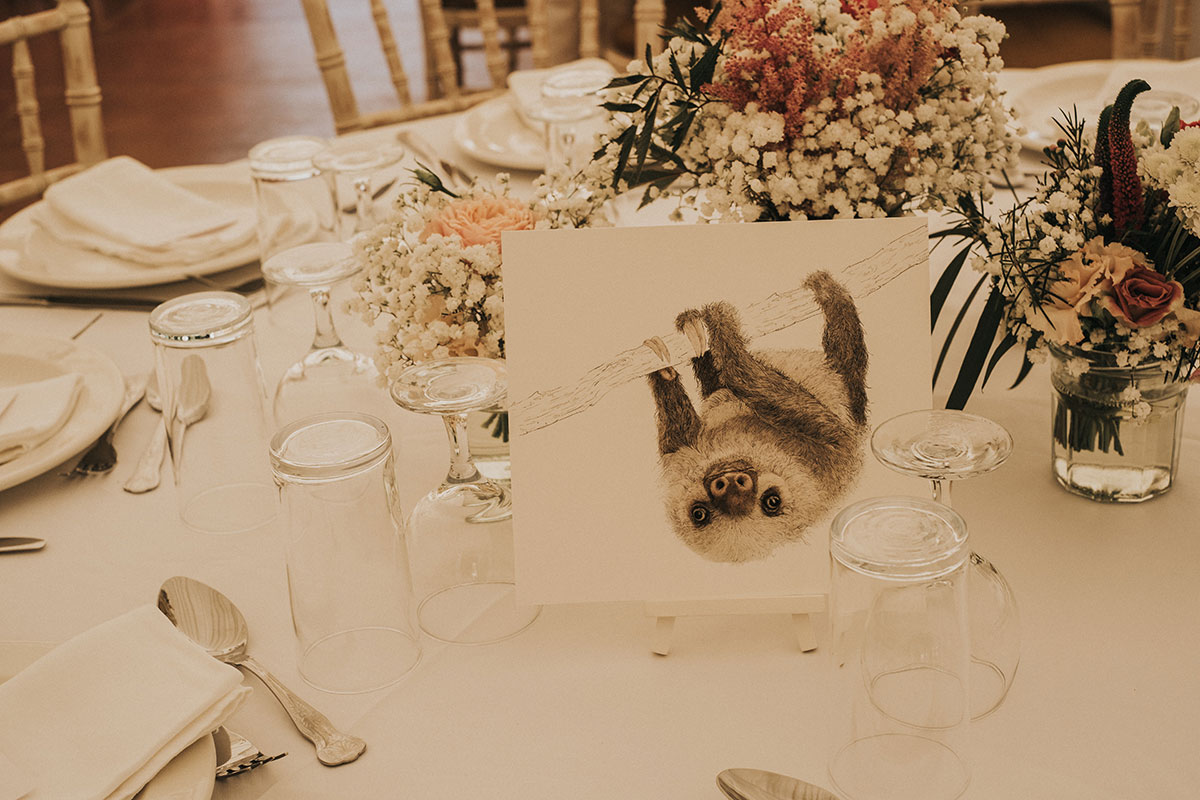 sloth illustrated wedding table sign surrounded by flowers in small glass vases