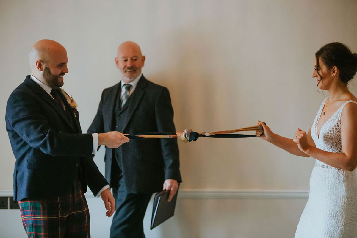 bride and groom completing hand fasting watched by celebrant