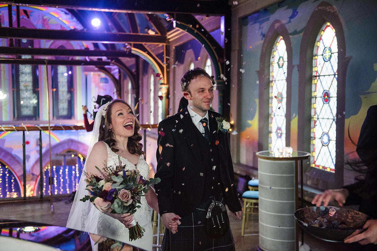 bride and groom laughing while being showered in confetti on mezzanine at Oran Mor
