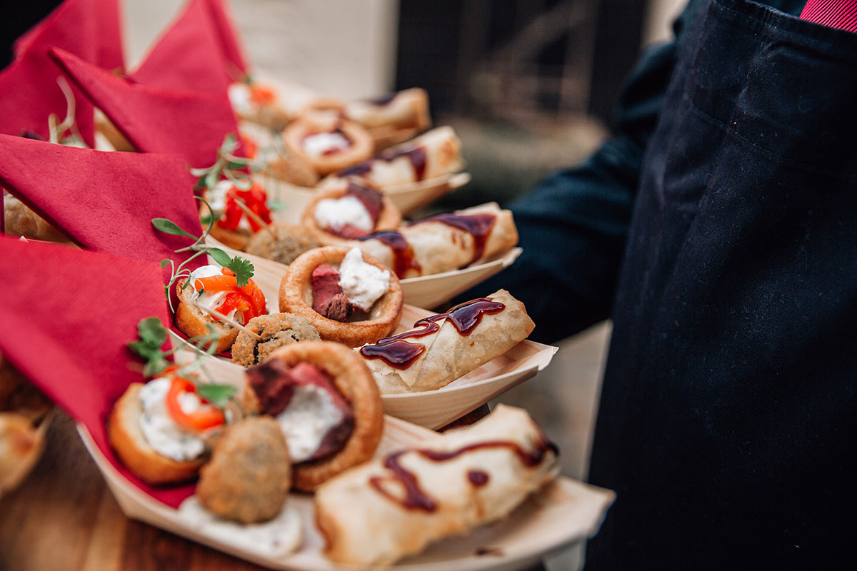 close up of wedding canapes with red napking being carried by person wearing black