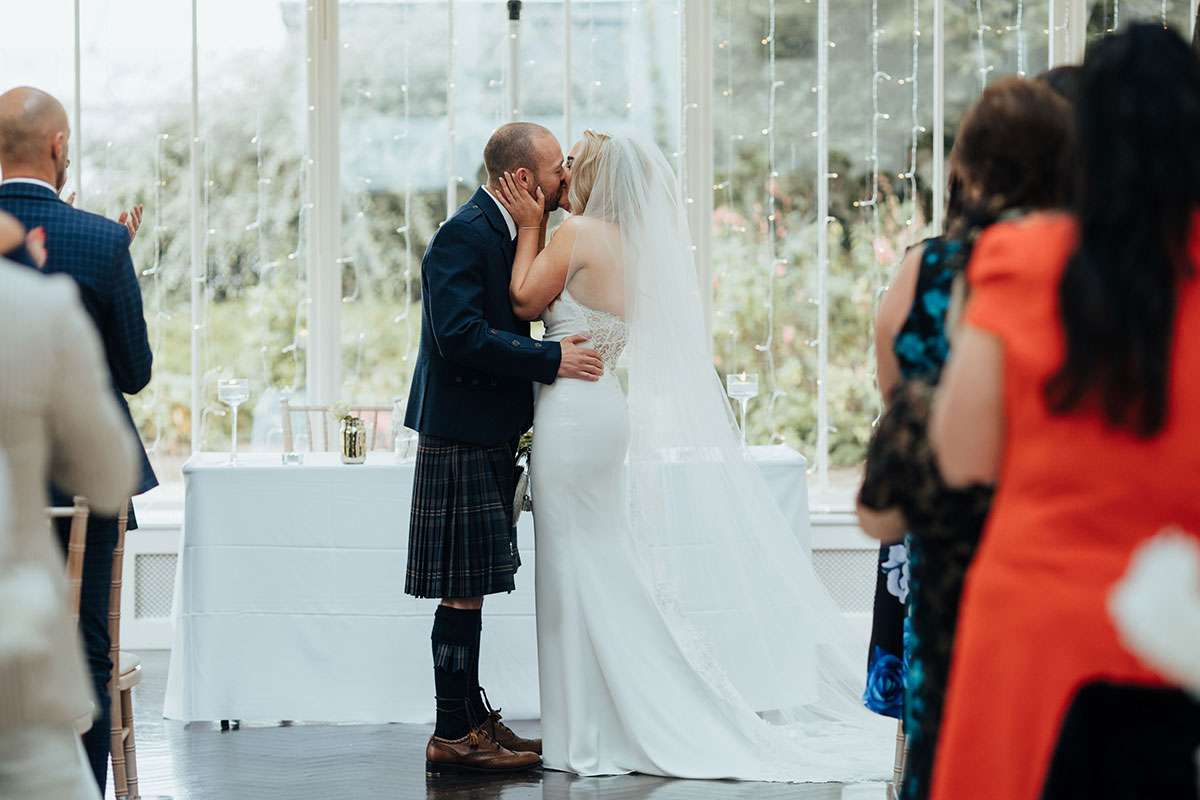 bride and groom kiss at wedding ceremony at Carlowrie Castle