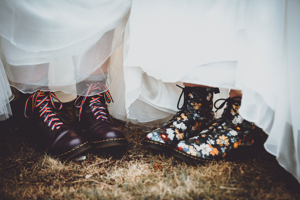 close up of brides wearing Doc Marten boots with rainbow laces and floral leather