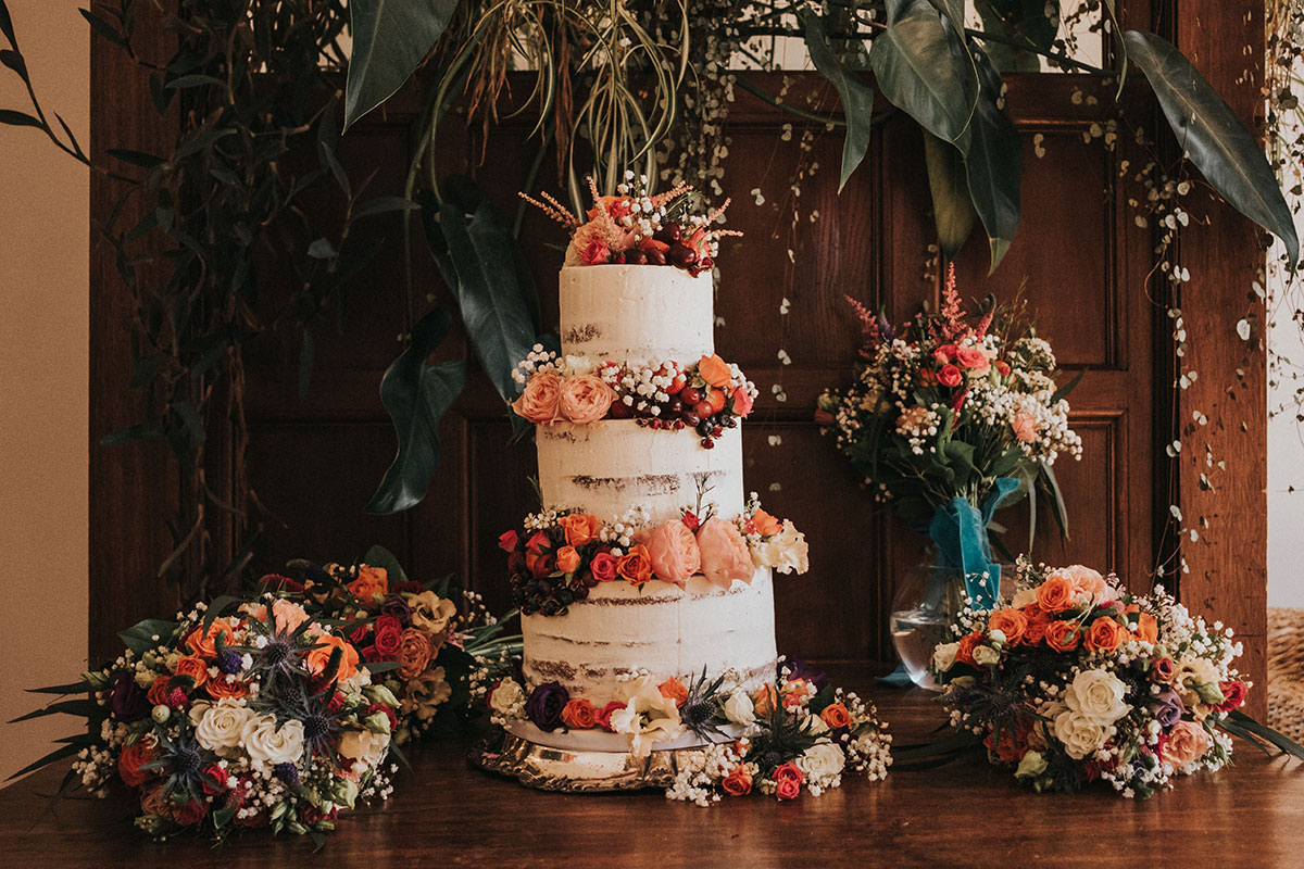 naked wedding cake by Rosewood Cake surrounded by matching flowers